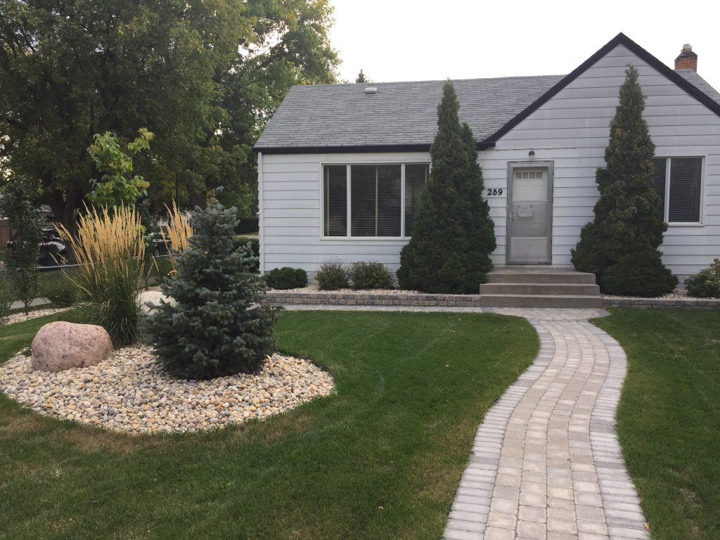 After the front yard is landscaped with an elegant brick walkway, stone island with feature rock and natural prairie grasses! Beautiful!