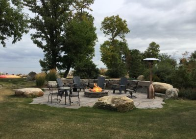 Grand flagstone lakefront patio with Rosetta Outcropping wall and belvedere fire pit