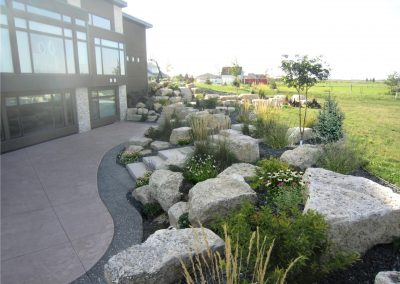 Limestone boulder retaining wall with dimensional concrete stairways