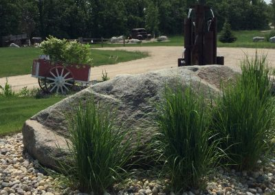 An impressive water fountain made from scrap steel pipe is the center piece to this country loop driveway
