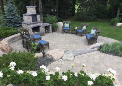 Barkman fireplace with side wood storage and roman paver patio