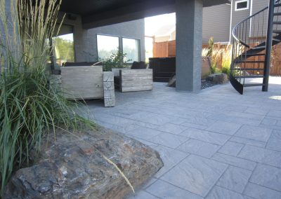 Paver patio and natural stone blending together as one
