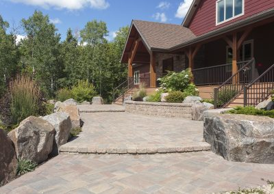 A series of paving stone landings create this grand entrance front patio area